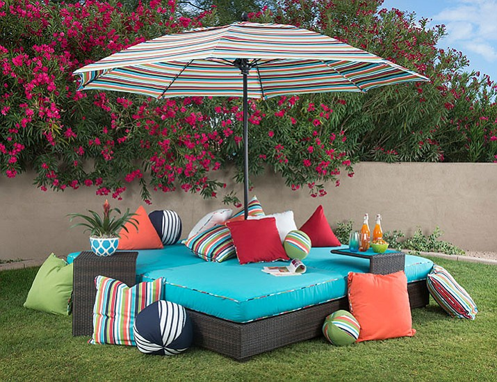 This May 2017 photo provided by Woodard shows a selection of colorful outdoor pillows displayed on the their new all-weather Lay N' Play lounger. (Photo provided by Woodard via AP)