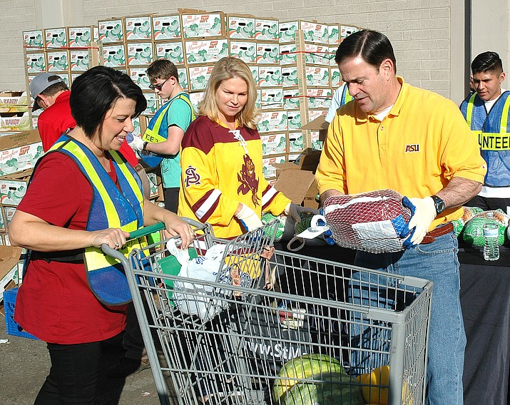 Gov. Doug Ducey and wife Angela, also wearing Arizona State University colors, help load turkeys into shopping carts Wednesday as part of the annual Thanksgiving food donation at St. Mary's Food Bank. Those carts eventually are wheeled to waiting vehicles.