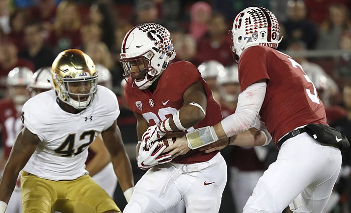 In this Nov. 25, 2017, file photo, Stanford quarterback K.J. Costello (3) hands off to Stanford running back Bryce Love (20) against Notre Dame during the first half in Stanford, Calif. (Tony Avelar/AP, File)