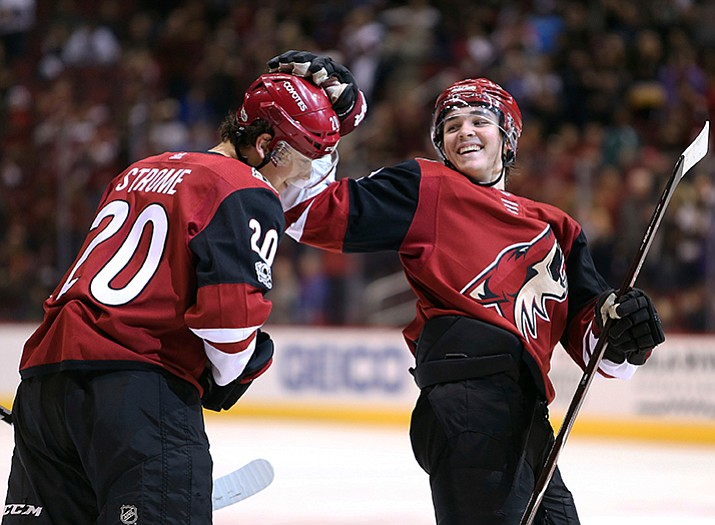 Arizona's Dylan Strome (20) gets a pat on the head from teammate Clayton Keller after scoring a goal against the New Jersey Devils during the third period of an NHL hockey game, Saturday, Dec. 2, in Glendale. The goal was Strome's first career NHL goal. The Coyotes defeated the Devils 5-0. (Ralph Freso/AP)