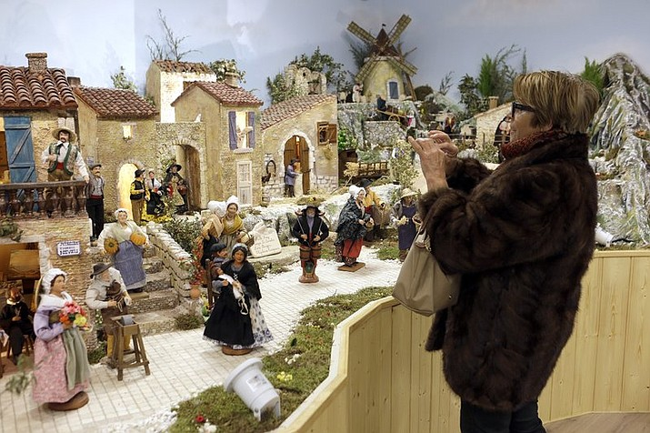 A woman photographs a crib in the village of Aubagne, near Marseille, southern France, Thursday, Nov. 30, 2017. Craftsmen of the city joined their forces to build a traditional provencal crib that shows 3 500 clay made figurines named santons. Santons are traditional colored figurines usually set in Christmas Nativity scenes. (AP Photo/Claude Paris)