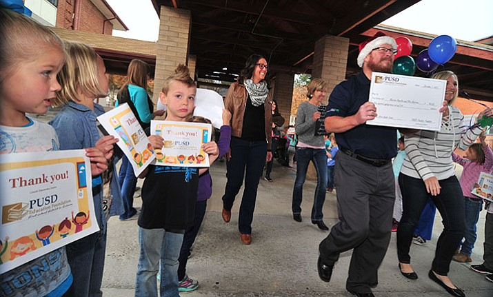 Superintendent Joe Howard leads the group at Lincoln Elementary School as the Prescott Unified School District Education Foundation traveled to different schools Friday to award grants. (Les Stukenberg/Courier)