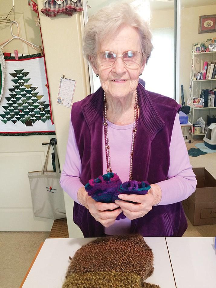 She holds up some of the fingerless gloves she makes for seniors. (Nanci Hutson/Courier)