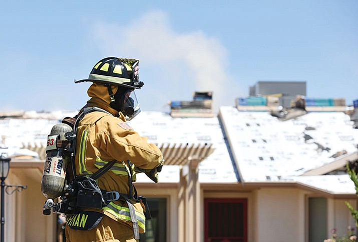 Central Yavapai fire fighters using their safety equipment not only against smoke but the harmful chemicals. (Les Stukenberg/Courier)