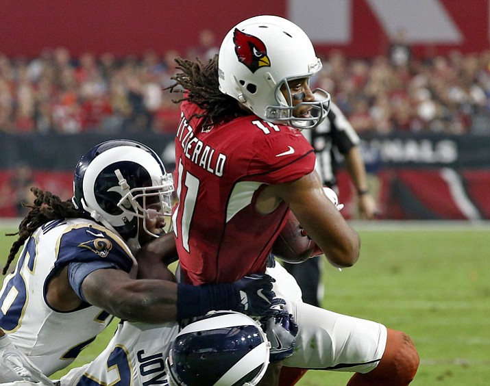 Arizona Cardinals wide receiver Larry Fitzgerald (11) is hit by Los Angeles Rams free safety Lamarcus Joyner (20) and Mark Barron during the first half Sunday, Dec. 3, 2017, in Glendale. (Ross D. Franklin/AP)