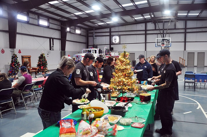 Golden Valley Fire District Firefighters and their family members take time out of their busy holiday schedules and work to enjoy dinner with each other at the annual Christmas Party for GVFD. Santa arrived in time to pass out presents to the young children in attendance.
