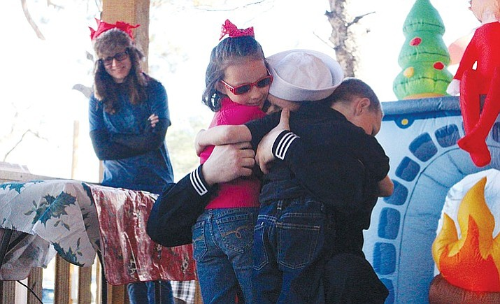 Alexis and Jeffery III greet their father, Jeffrey Havenner Jr., who returned to Kingman after 14 months of serving on a U.S. Navy submarine. The children had asked to have Dad as their Christmas present. (Claire Whitley/Kingman Daily Miner)
