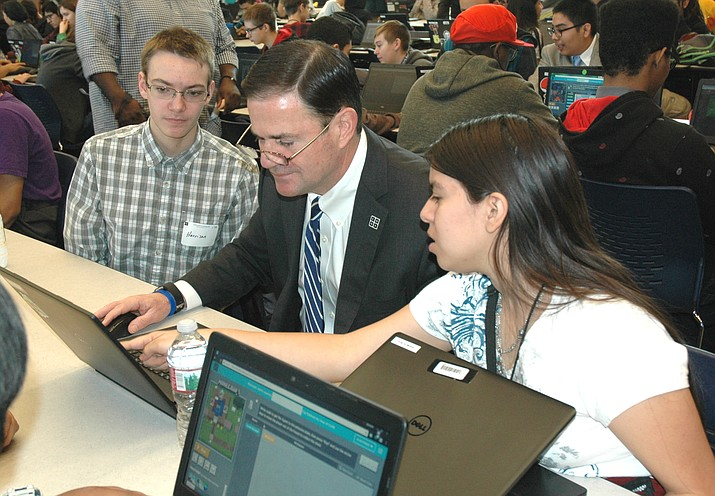 Harrison Kerkhoff and Eligia (Ellie) De La Cruz help Gov. Doug Ducey complete a coding task. Ducey visited the Phoenix Coding Academy Monday to praise what is being taught even though none of the funds came from the state.
