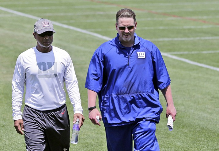 In this June 13, 2017, file photo, New York Giants head coach Ben McAdoo, right, and general manager Jerry Reese walk off the field after NFL football practice in East Rutherford, N.J. A person familiar with the situation says Ben McAdoo has been fired as coach of the New York Giants and Jerry Reese is out as general manager less than a year after taking the team to the playoffs for the first time since 2011. McAdoo and Reese were fired Monday, Dec. 4, 2017, a day after the Giants were beaten in Oakland and dropped to 2-10, according to the person who spoke on condition of anonymity because the team had not made an official announcement. (Seth Wenig/AP, File)
