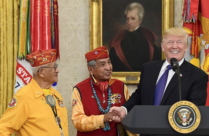 President Donald Trump, right, meets with Navajo Code Talkers Peter MacDonald, center, and Thomas Begay, left, in the Oval Office of the White House in Washington, Monday, Nov. 27, 2017. 