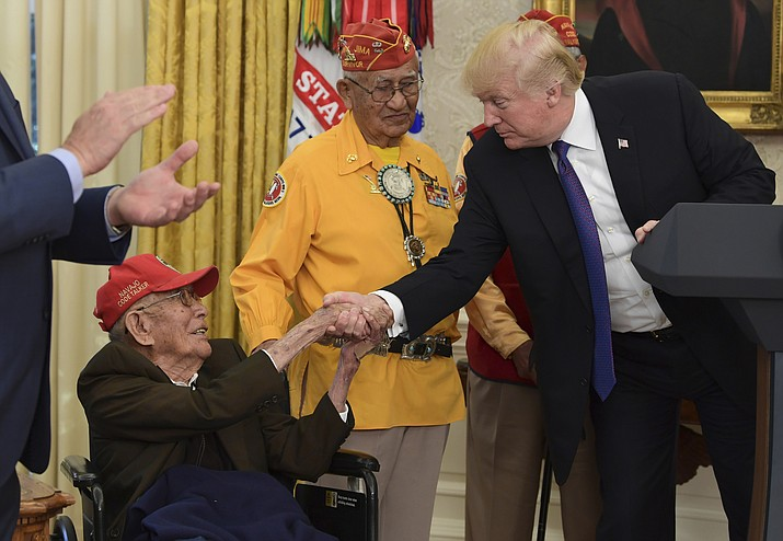 President Donald Trump meets with Navajo Code Talkers, Fleming Begaye Sr., seated and Thomas Begay, center, in the Oval Office of the White House in Washington, Monday, Nov. 27, 2017. AP Photo/Susan Walsh