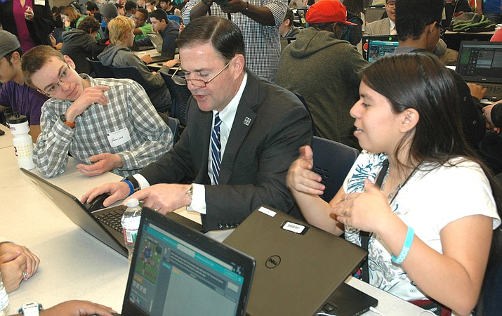 Harrison Kerkhoff and Eligia (Ellie) De La Cruz help Gov. Doug Ducey complete a coding task. Ducey visited the Phoenix Coding Academy Monday to praise what is being taught even though none of the funds came from the state. (Capitol Media Services photo by Howard Fischer)
