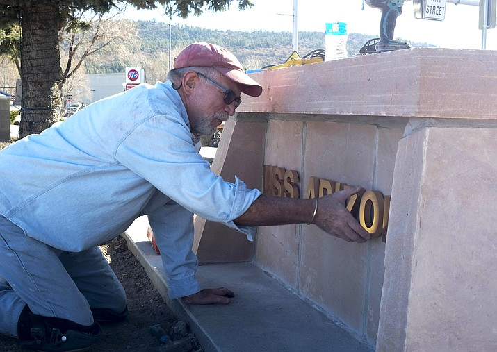 John Holst places the letters on the new USS Arizona display.