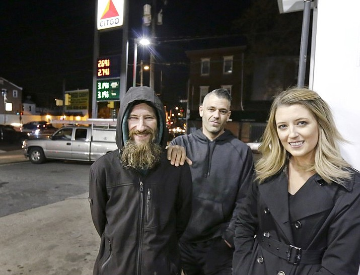 In this Nov. 17, 2017, photo, Johnny Bobbitt Jr., left, Kate McClure, right, and McClure's boyfriend Mark D'Amico pose at a Citgo station in Philadelphia. When McClure ran out of gas, Bobbitt, who is homeless, gave his last $20 to buy gas for her. McClure started a Gofundme.com campaign for Bobbitt that has raised more than $275,000. (Elizabeth Robertson/The Philadelphia Inquirer via AP, File)
