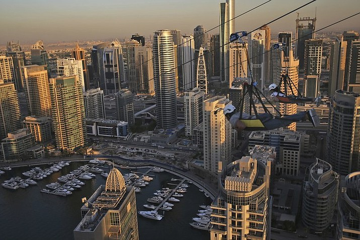 Two people ride the world's longest urban zip line with a speed of up to 80 kilometers per hour on a one kilometer run from 170 meter to ground level, at the Marina district of Dubai, United Arab Emirates, Tuesday, Dec. 5, 2017. (AP Photo/Kamran Jebreili)