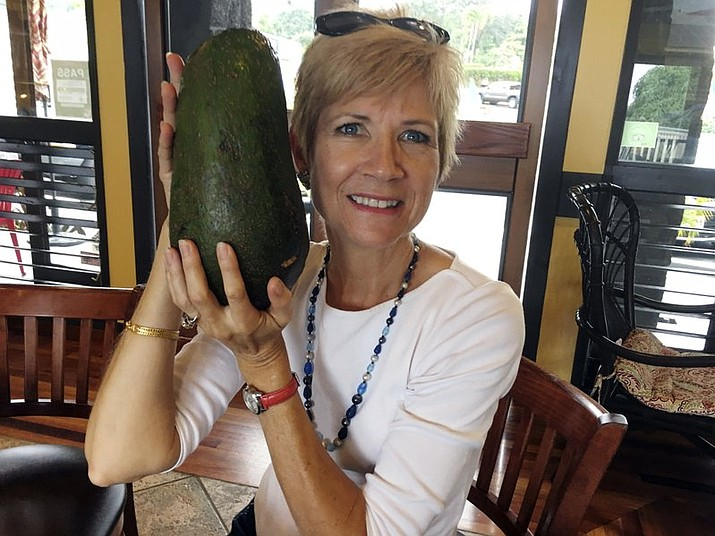 Pamela Wang poses for a photo in Kealakekua, Hawaii, with an avocado she found while on a walk. Wang is waiting to hear back from Guinness World Records to find out if the 5-pound (2.3-kilogram) avocado she snagged is the world's largest. (AP Photo/Mary Lou Knurek)