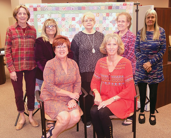 From left to right back row, Debbie Burnham-Kidwell, Pat Mullen-Lamb, Kathy Cook, Phyllis Eaton and Eve Cragen.  Seated front from left to right Krystal Burge and Betsy Parker. The members of the steering committee stand in front of a quilt which is raffled every year to support scholarships. The quilt is the work of Karen Goudy.