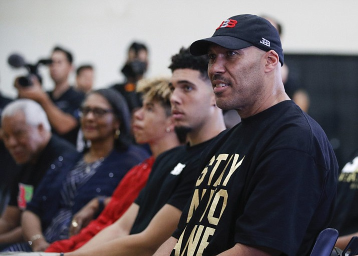 In this June 23, 2017, file photo, LaVar Ball, right, father of Los Angeles Lakers draft pick Lonzo Ball, listens to his son during the NBA basketball team's news conference in El Segundo, Calif. Mr. Ball removed his son, LiAngelo, from UCLA on Monday, Dec. 4, 2017. (Jae C. Hong, File/AP)