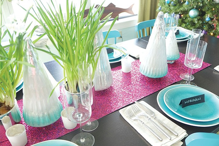This undated photo provided by Massachusetts-based interior designer Kristina Crestin shows a table setup by Crestin. To add some unexpected sparkle to a holiday table, Crestin used sheets of raspberry-colored metallic craft paper as a table runner paired with paperwhite plants in silver-toned metal pots. (Kristina Crestin via AP)