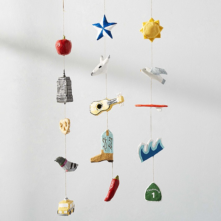 This undated photo provided by West Elm shows a mobile by Los Angeles artist Kim Baise, where she sculpts mini versions of objects like ukuleles, fruit, birds and cowboy boots out of papier mache, then strings them into the playful mobiles. Showcasing decorative elements that are quirky, creative and fun give a boho nursery a unique look. (West Elm via AP)