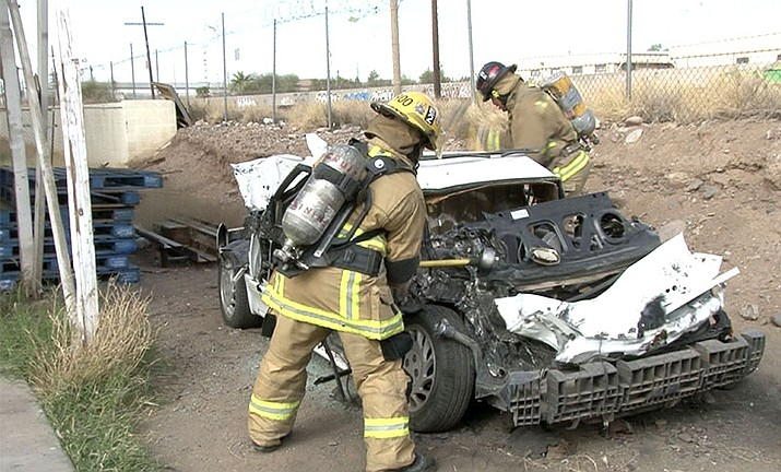 Firefighters pound on a car to practice accuracy when wielding an ax at a Phoenix gym that helps keep firefighters in shape.