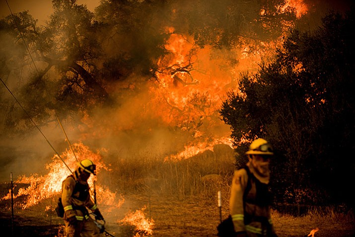 Firefighters light backfire while trying to keep a wildfire from jumping Santa Ana Rd. near Ventura, Calif., on Saturday, Dec. 9, 2017. (AP Photo/Noah Berger)