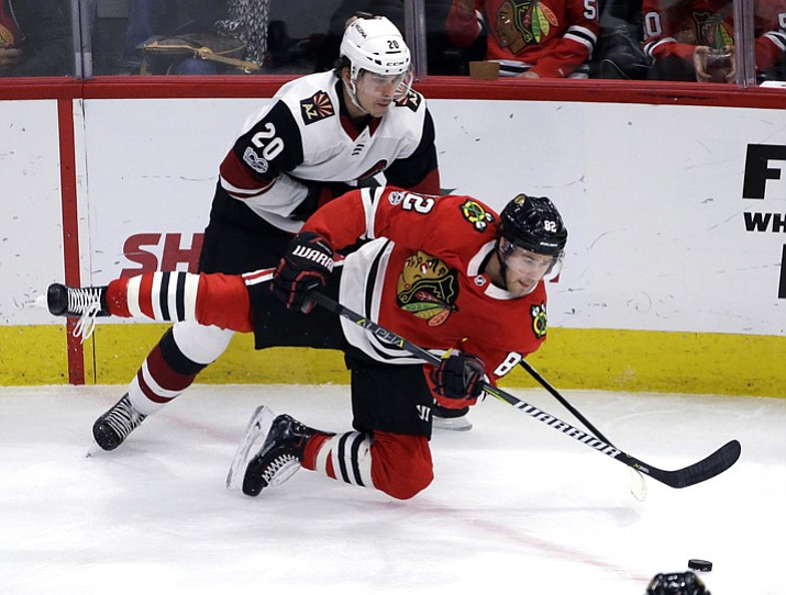 Chicago Blackhawks defenseman Jordan Oesterle, front, is checked by Arizona Coyotes center Dylan Strome during the first period of an NHL hockey game Sunday, Dec. 10, 2017, in Chicago. (Nam Y. Huh/AP)
