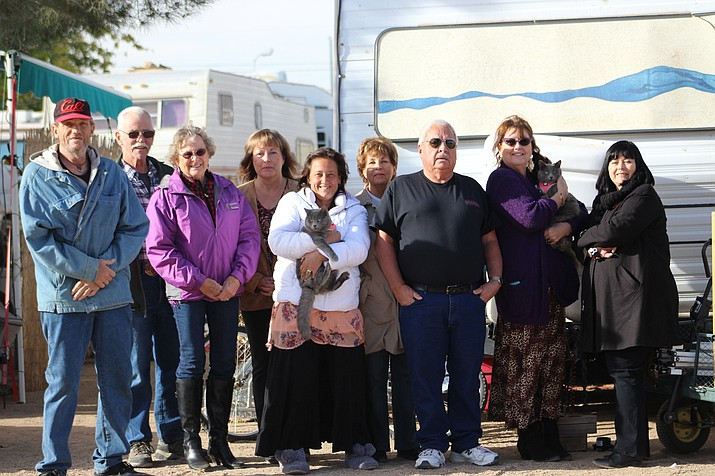 "Bill, left, and Shellie, center in white, stand in front of their travel trailer with part of the group Diane Pherigo has dubbed the ""Christmas Angels."""
