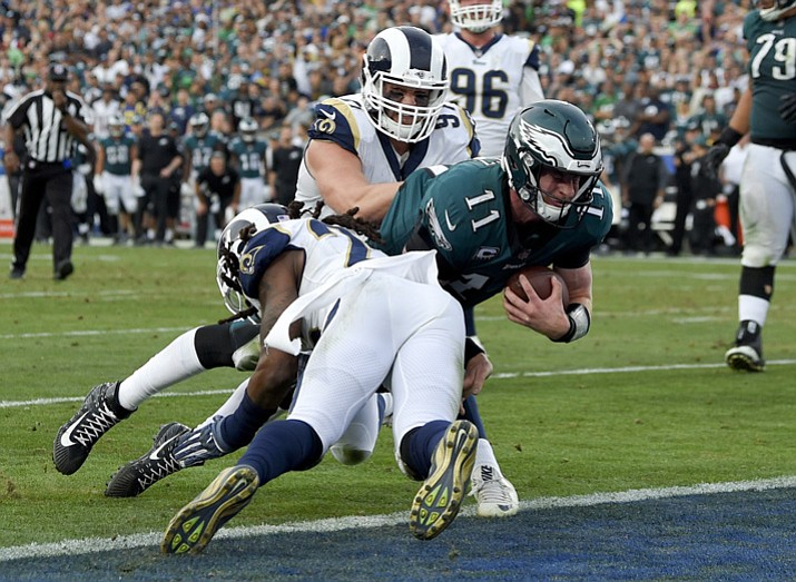 Philadelphia Eagles quarterback Carson Wentz gets tackles during the second half of an NFL football game against the Los Angeles Rams Sunday, Dec. 10, 2017, in Los Angeles. Wentz left the game shortly after the play and did not return to the game. (Mark J. Terrill/AP)