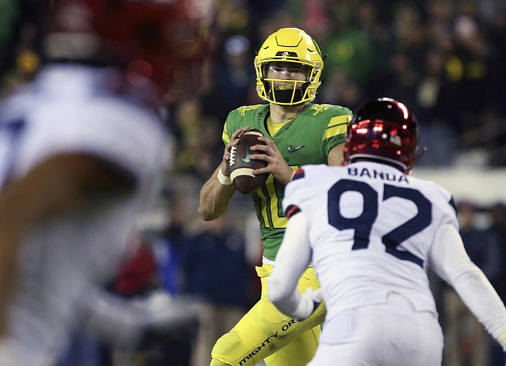 In this Nov. 18, 2017, file photo, Oregon quarterback Justin Herbert looks to pass the ball against Arizona during the fourth quarter of an NCAA college football game in Eugene, Ore. Herbert was on his way to a big sophomore year when he broke his collarbone midway through this season. Without him, the Ducks went 1-4. In the seven games he played, Herbert passed for 1,750 yards and 13 touchdowns and added five rushing touchdowns. (Chris Pietsch/AP, File)