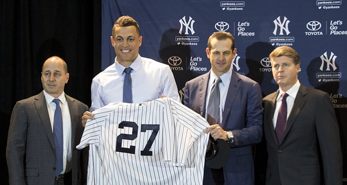 Yankees General Manager Brian Cashman, left, stands next to new Yankee Giancarlo Stanton, center, and his new jersey with Yankee Manager Aaron Boone, right middle, and Yankee Owner Hal Steinbrenner, right, during the Major League Baseball winter meetings Monday, Dec. 11, 2017, in Orlando, Fla. (Willie J. Allen Jr./AP)