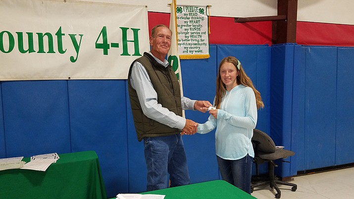 Mohave County Supervisor Gary Watson presents the 4-H Achievement Award to Brooke Forsse of the Cactus Critters at the annual recognition program.