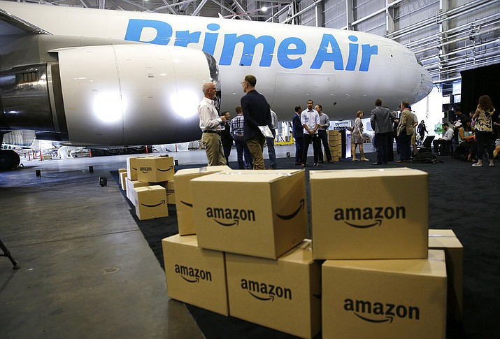 "In this photo, Amazon.com boxes are shown stacked near a Boeing 767 Amazon ""Prime Air"" cargo plane on display in a Boeing hangar in Seattle. With Christmas 2017 on a Monday, most retailers have one less day to get packages delivered on time. Retailers have been trying to speed up delivery as they try to replicate the service offered by Amazon. (AP Photo/Ted S. Warren, File)"