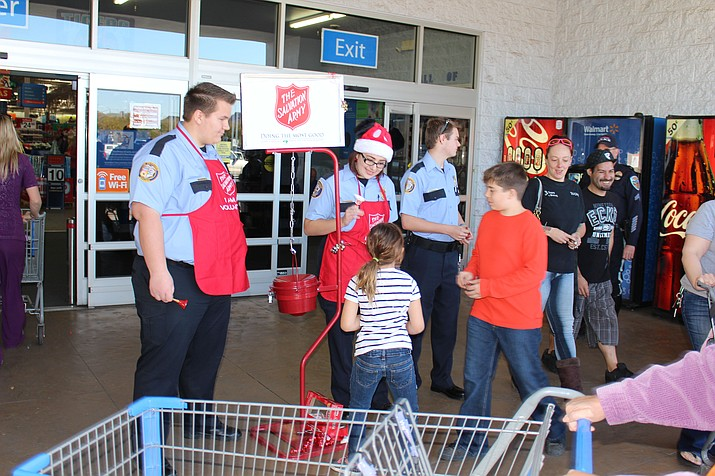 From left, Dean Curtis, Lilith Bennett and Trevin Gravell of Kingman Police Department Explorers ring the bell Friday for the Salvation Army's Red Kettle drive in front of Walmart.
