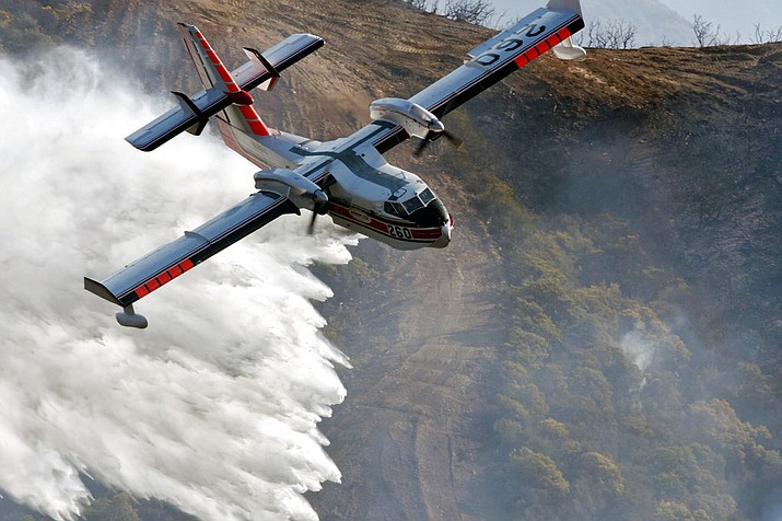 A Bombardier 415 Super Scooper makes a water drop on hot spots along the hillside east of Gibraltar Road in Santa Barbara, Calif., Sunday morning, Dec. 17, 2017. Wind gusts of up to 52 mph have been recorded in the area using a hand held weather device. The Office of Emergency Services announced the orders Saturday as Santa Ana winds pushed the fire close to the community. The mandatory evacuation zone is now 17 miles long and up to 5 miles wide, extending from coastal mountains northwest of Los Angeles to the ocean. Winds in the foothill area are hitting around 30 mph, with gusts up to 60 mph. (Mike Eliason/Santa Barbara County Fire Department)