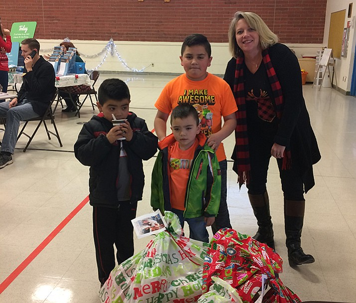 PUSD Grants Specialist Kelly Mattox stands with three children in the Sanchez family: Jose (center), 9, Osile, 4, (standing in the front) and Aaron, 7, (left). (Courier/Nanci Hutson)