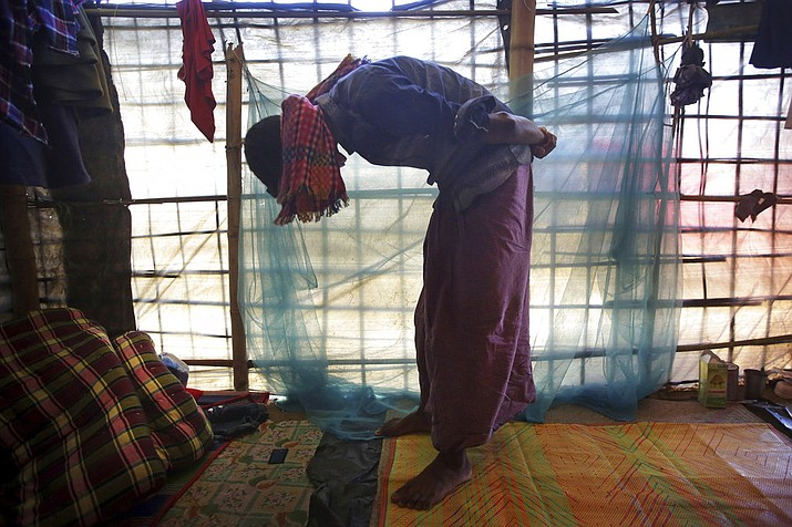 In this photo, Mohamed Yaha, 18, demonstrates to The Associated Press in his tent in Jamtoli refugee camp in Bangladesh, what he saw when soldiers bound the hands of dozens of men behind their backs with nylon rope and blindfolded them with scarves taken from the women when they massacred his village Maung Nu, in Myanmar's Rakhine State. More than 650,000 Rohingya Muslims have fled to Bangladesh from Myanmar since August, and many have brought with them stories of atrocities committed by security forces in Myanmar, including an Aug. 27 army massacre that reportedly took place in the village of Maung Nu. (AP Photo/Wong Maye-E)