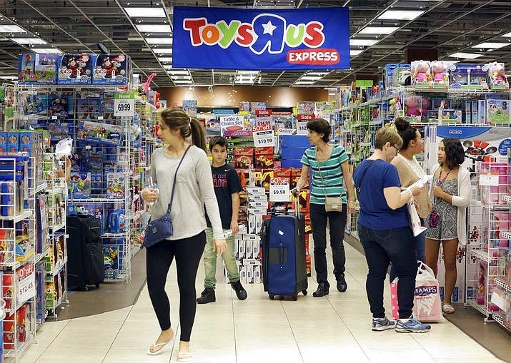 FILE - In this file photo, shoppers browse at a Toys R Us store in Miami. The toys your kids unwrap this Christmas could invite hackers into your home. That Grinch-like warning comes from the FBI, which said this summer that toys connected to the internet could be a target for crooks who may listen in on conversations or use them to steal a child's personal information. (AP Photo/Alan Diaz, File)