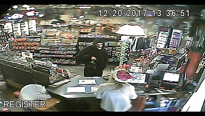 A man wearing a bandanna as mask and carrying a holstered gun, caught on surveillance video, took an undisclosed amount of cash from the 76 Service Station in the 35000 block of Old Black Canyon Highway Wednesday, Dec. 20.