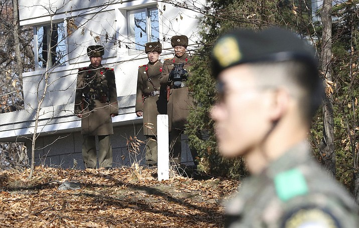 FILE - In this file photo, North Korean soldiers look at the South side as a South Korean stands guard near the spot where a North Korean soldier crossed the border on Nov. 13 at the Panmunjom, in the Demilitarized Zone, South Korea. South Korea says on Thursday, Dec. 21, 2017, it has fired 20 rounds of warning shots as North Korean soldiers approached a military demarcation line at the border after their comrade defected to South Korea. (AP Photo/Lee Jin-man, File)