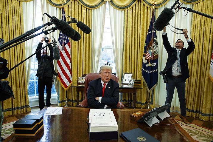 President Donald Trump speaks to reporters after signing the tax bill and continuing resolution to fund the government, in the Oval Office of the White House, Friday, Dec. 22, 2017, in Washington. (AP Photo/Evan Vucci)