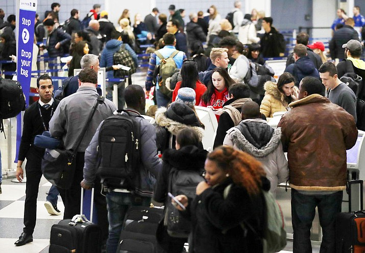 Travelers check and walk in Terminal 1 at O'Hare International Airport Thursday, Dec. 21, 2017, in Chicago. (AP Photo/Nam Y. Huh)
