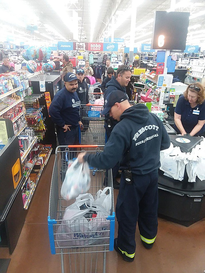 Prescott firefighters check out at Walmart on Saturday, Dec. 23, buying clothes and other items for a local family that was displaced Friday by a house fire.