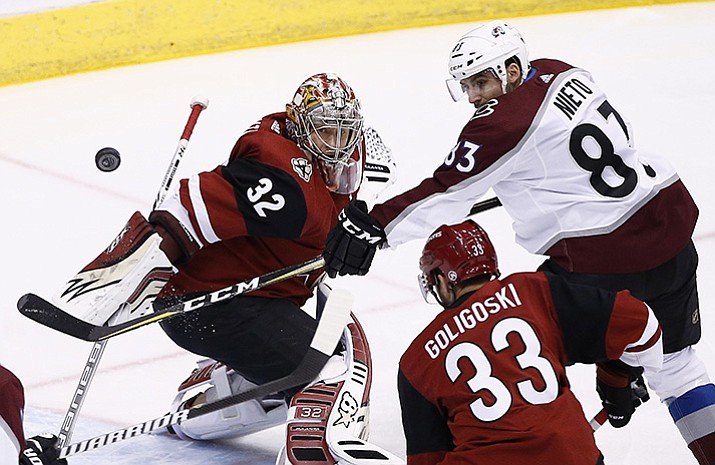 Colorado Avalanche left wing Matt Nieto (83) tries to redirect the puck as Arizona Coyotes goalie Antti Raanta (32) moves in to stop the puck while Coyotes defenseman Alex Goligoski (33) watches during the first period of an NHL hockey game, Saturday, Dec. 23, 2017, in Glendale.