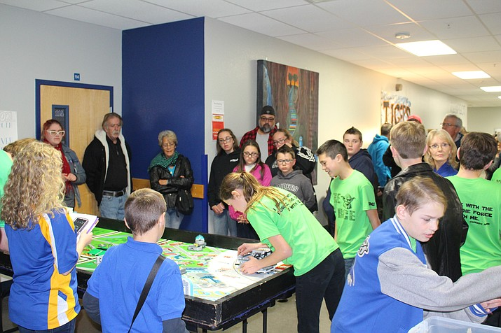 Margret Scholl, an eighth-grader with the Kingman Academy Middle School First Lego League team, The Force, puts her robot on course as parents and team supporters watch during an open house last week.