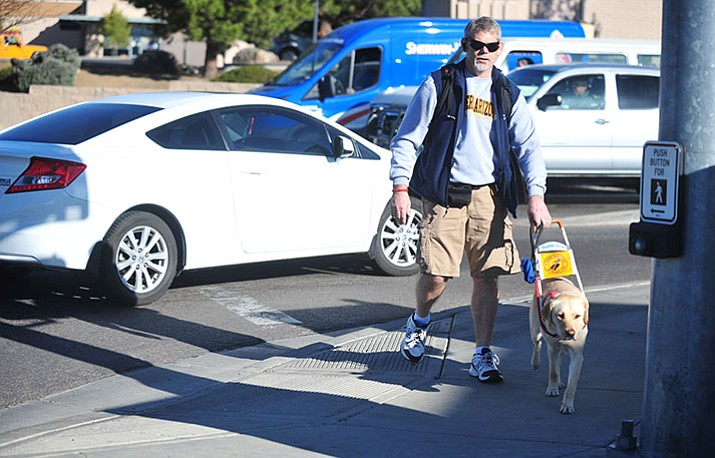 Doug Reber and his seeing eye dog Bay cross Gail Gardner at Iron Springs Road. There's a proposal to make it illegal to misrepresent your pet as a service animal. (Les Stukenberg/Courier file)