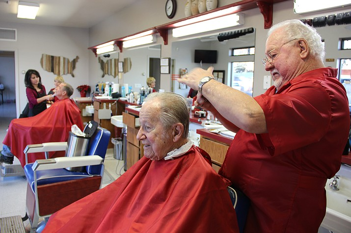 Roger Gibson (right) cutting a customer's hair on his last day in the business on Friday, Dec. 22. As of this week, Gibson has officially handed over his business, Roger's Modern Barbershop, to Angela Maldonado (cutting hair in the background), so he may retire at the age of 75.
