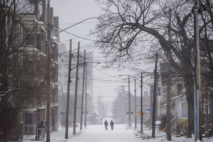 Pedestrians walk down the centre of the road in Moncton, N.B., as a winter storm blows through Atlantic Canada on Christmas Day, Monday, Dec. 25, 2017. (Darren Calabrese/The Canadian Press via AP)