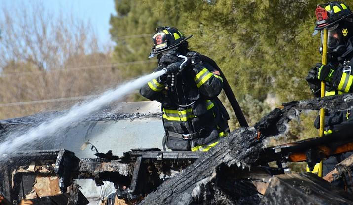 Firefighters put out the remains of a house fire in Camp Verde that destroyed a home two days before Christmas on Pike Street. VVN/Vyto Starinskas