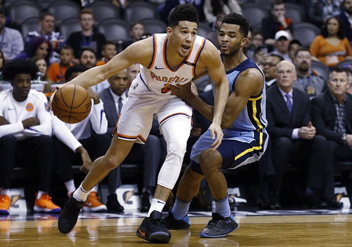 Back from injury, Phoenix Suns guard Devin Booker (1) dribbles past Memphis Grizzlies guard Andrew Harrison, right, during the first half Tuesday, Dec. 26, 2017, in Phoenix. (Ross D. Franklin/AP)